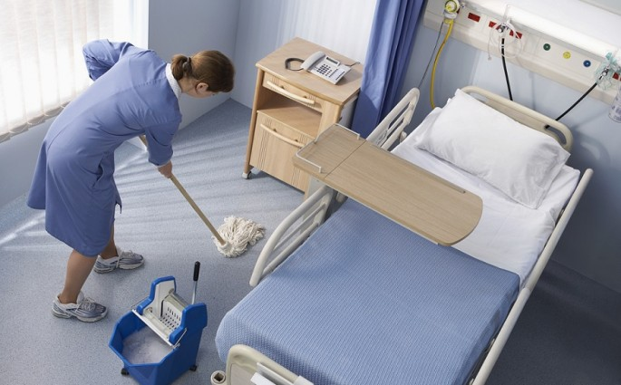 Maid Mops the Floor by a Hospital Bed