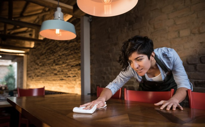 Happy waitress cleaning a table while working at a restaurant